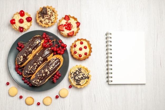Bovenaanzicht van chocolade-eclairs en aalbessen op de grijze plaat omringd met taartjes en koekjes en een notitieblok op de witte houten tafel met kopie ruimte