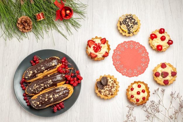 Bovenaanzicht van chocolade-eclairs en krenten op de grijze plaat, het rode ovale kanten kleedje afgerond met taartjes en dennenboombladeren met kerstspeelgoed op de witte houten grond