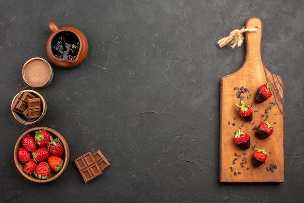 Bovenaanzicht van chocolade en aardbeien in de verte, aardbeien en chocoladeroom aan de linkerkant en smakelijke met chocolade omhulde aardbeien op de houten snijplank aan de rechterkant