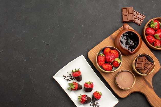 Bovenaanzicht van chocolade in de verte aan boord van met chocolade bedekte aardbeien op plaat naast de snijplank met chocoladeroom en aardbeien en chocoladerepen