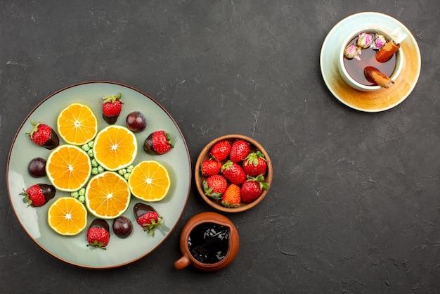Bovenaanzicht van chocolade in de verte en fruit gehakte sinaasappel met chocolade bedekte aardbei groene snoepjes en kommen chocoladesaus en aardbeien en een kopje thee met kaneelstokjes