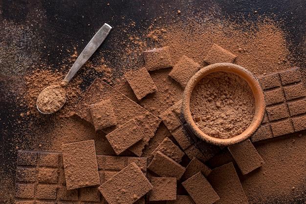 Bovenaanzicht van chocolade met kom cacaopoeder en lepel