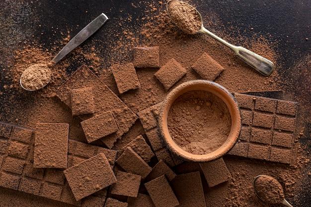 Bovenaanzicht van chocolade met kom cacaopoeder en lepels