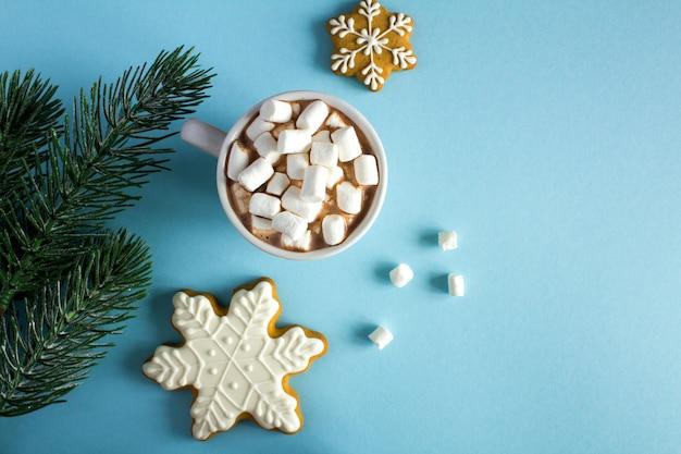 Bovenaanzicht van chocolade met marshmallows op een blauwe ondergrond