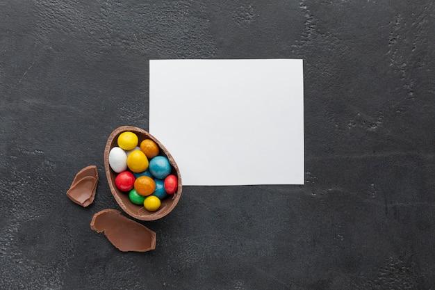 Bovenaanzicht van chocolade paasei gevuld met kleurrijke snoep