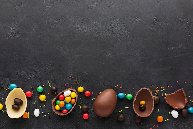 Bovenaanzicht van chocolade paaseieren gevuld met kleurrijke snoep
