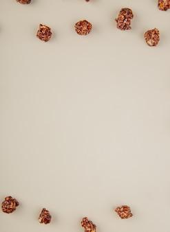 Bovenaanzicht van chocolade popcorn op wit met kopie ruimte 1