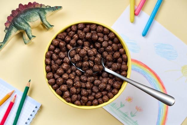 Bovenaanzicht van chocoladecornflakes in een gele kom met kinderspullen op een lichtgele achtergrond