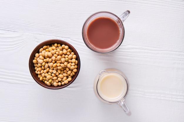 Bovenaanzicht van chocolademelk en sojamelk in glas op witte tafel