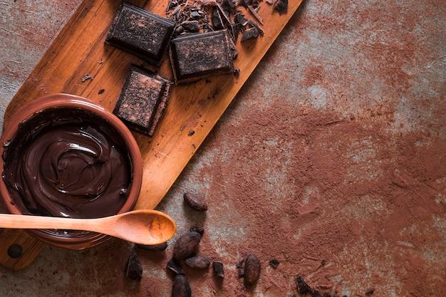 Bovenaanzicht van chocoladeroom en stukken op rommelige tafel