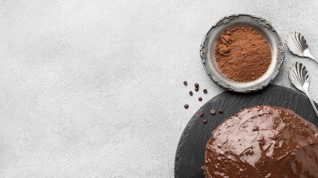 Bovenaanzicht van chocoladetaart met cacaopoeder en kopie ruimte
