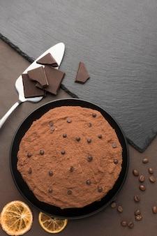 Bovenaanzicht van chocoladetaart met cacaopoeder en spatel