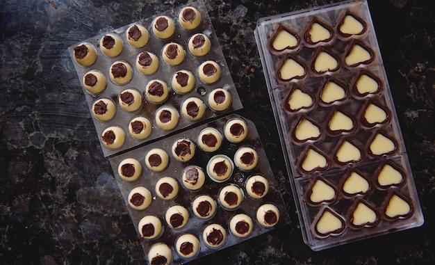 Bovenaanzicht van chocoladevormen met vulling op een marmeren oppervlak voor het temperen van gesmolten chocolademassa. concept van de viering van chocolade werelddag