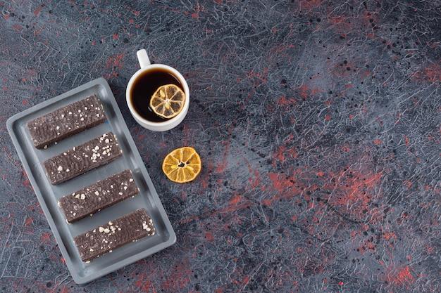 Bovenaanzicht van chocoladewafels en kopje geurige thee op rustiek.