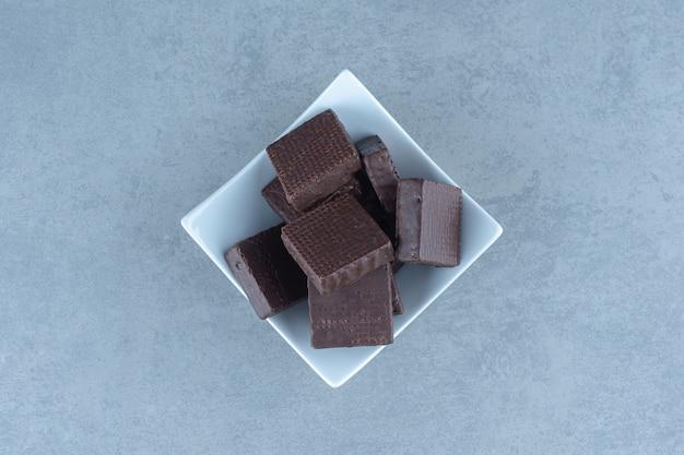 Bovenaanzicht van chocoladewafels in witte kom.