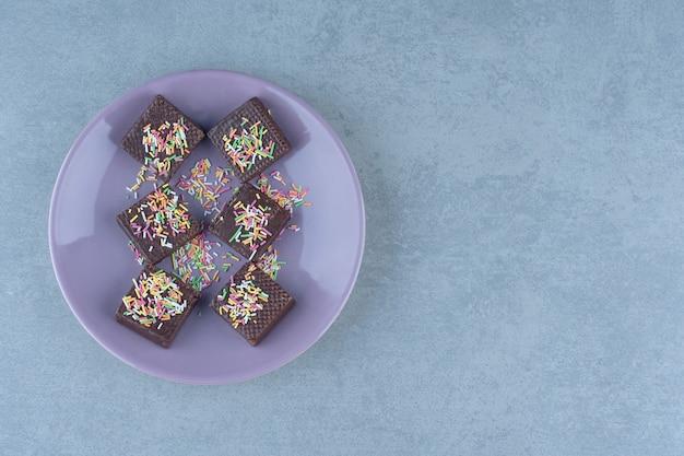 Bovenaanzicht van chocoladewafels met strooi op paarse plaat.