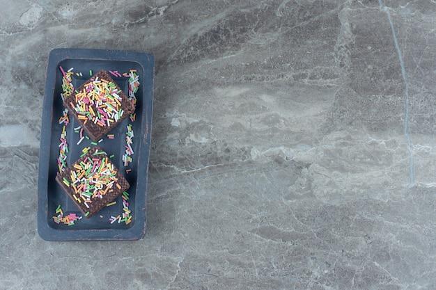 Bovenaanzicht van chocoladewafels op grijs houten bord.