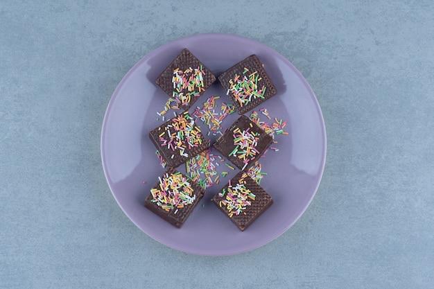 Bovenaanzicht van chocoladewafels op paarse plaat.