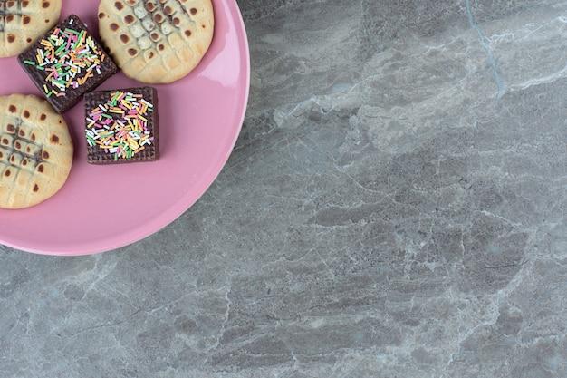 Bovenaanzicht van chocoladewafeltje en koekjes op roze plaat.