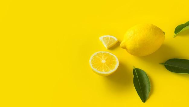 Bovenaanzicht van citroen en bladeren op gele achtergrond.