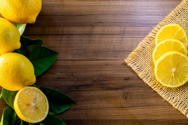Bovenaanzicht van citroen en groene bladeren op houten tafel