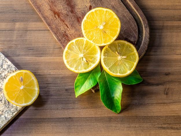 Bovenaanzicht van citroenen en groene bladeren op houten oppervlak