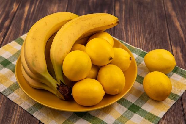 Bovenaanzicht van citroenen met afgeronde vorm op een gele plaat op een gecontroleerde doek met bananen op een houten oppervlak