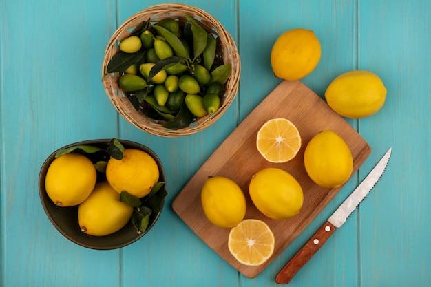 Bovenaanzicht van citroenen met afgeronde vorm op een kom met citroenen geïsoleerd op een houten keukenplank met mes met kinkans op een emmer op een blauwe houten muur