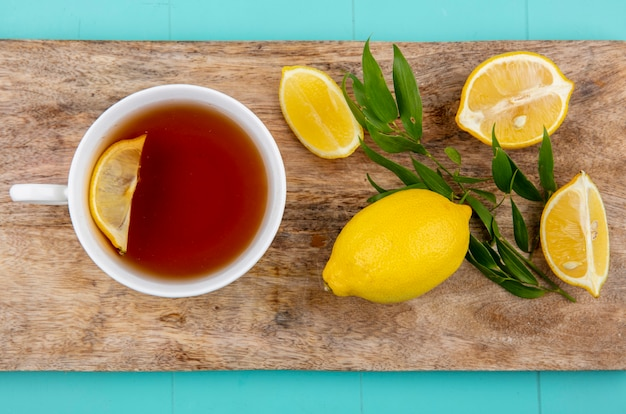 Bovenaanzicht van citroenen met dragon op een houten keuken bord met een kopje thee op blauwe ondergrond