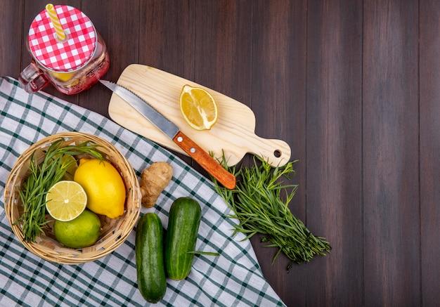 Bovenaanzicht van citroenen op een emmer met dragon groen op een gecontroleerd tafelkleed met komkommers op een houten oppervlak