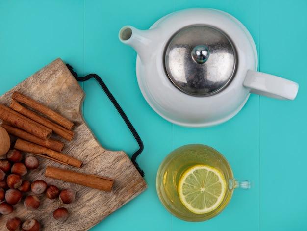 Bovenaanzicht van citroensap met schijfje citroen in glazen beker en noten kaneel walnoot op snijplank met theepot op blauwe achtergrond