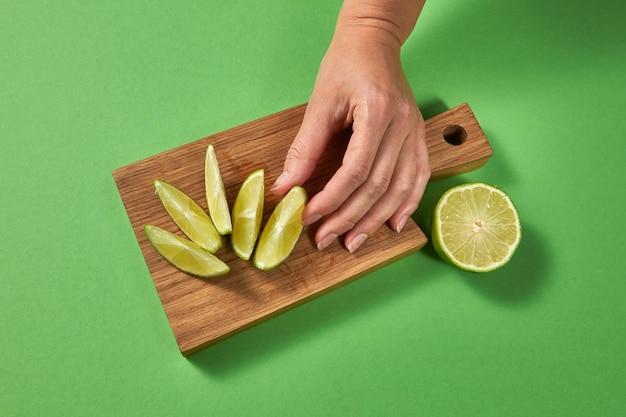 Bovenaanzicht van citrusmuur. schijfjes limoen op een bord op een groene tafel. een vrouwelijke hand zet schijfje rijpe verse groene limoen op een houten snijplank met kopie ruimte. Premium Foto