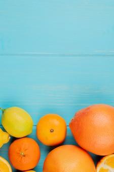 Bovenaanzicht van citrusvruchten als oranje citroen en mandarijn op blauwe achtergrond met kopie ruimte