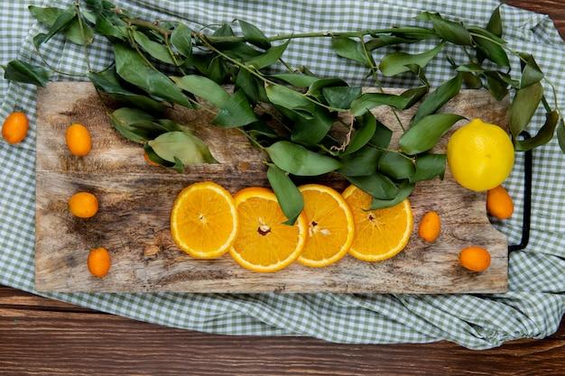 Bovenaanzicht van citrusvruchten als oranje citroen kumquat met bladeren op snijplank op doek en houten achtergrond