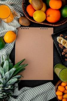 Bovenaanzicht van citrusvruchten als oranje kiwi ananas op doek oppervlak met kopie ruimte