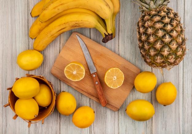 Bovenaanzicht van citrusvruchten citroenen op een emmer met halve citroen op een houten keukenplank met mes met citroenen, bananen en ananas geïsoleerd op een grijze houten achtergrond