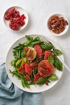 Bovenaanzicht van citrusvruchten salade met noten, groene slablaadjes. evenwichtig eten. spinazie met sinaasappel, grapefruit, pecannoten en granaatappelpitjes in kom op tafel met wit tafellaken.