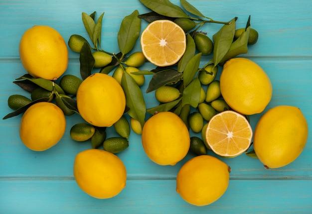 Bovenaanzicht van citrusvruchten zoals kinkans en citroenen met bladeren geïsoleerd op een blauw houten oppervlak