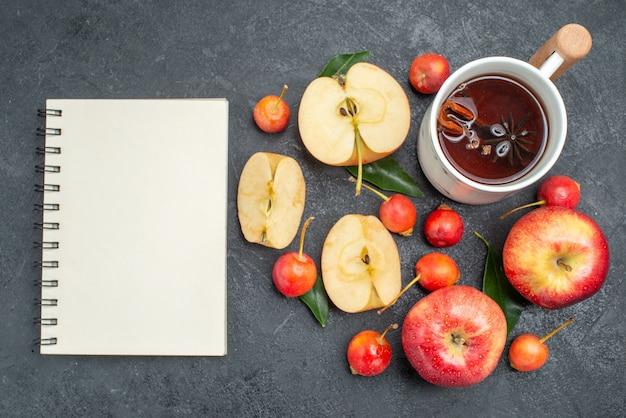 Bovenaanzicht van close-up fruit een kopje thee appels kersen met bladeren witte notebook