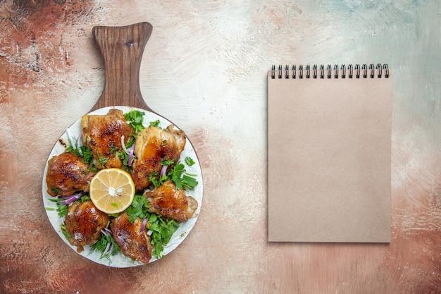 Bovenaanzicht van close-up kip een smakelijke kip met citroenkruiden op lavash op het bord crème notitieboekje