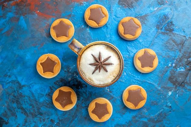 Bovenaanzicht van close-up snoep een kopje koffie en koekjes eromheen