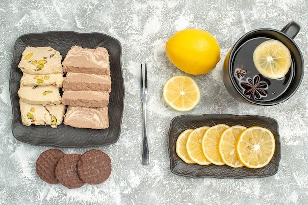 Bovenaanzicht van close-up snoep een kopje thee citroen vork koekjes zonnebloempitten halva
