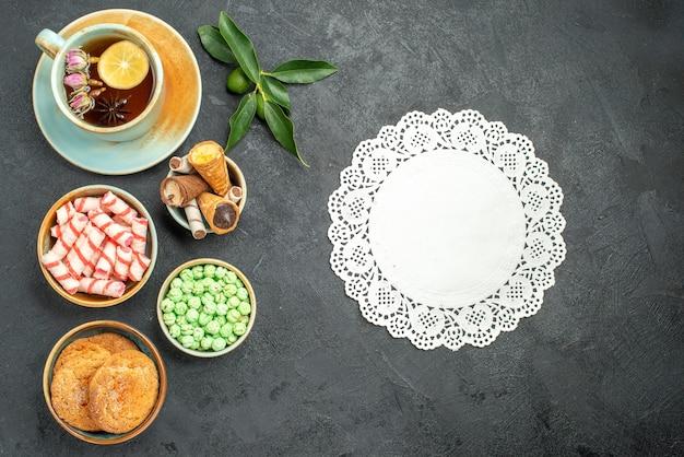 Bovenaanzicht van close-up snoep een kopje thee koekjes wafels snoepjes citrusvruchten kant kleedje