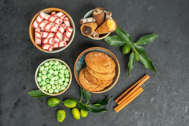 Bovenaanzicht van close-up snoepjes citrusvruchten met bladeren kaneel kleurrijke snoepjes wafels koekjes