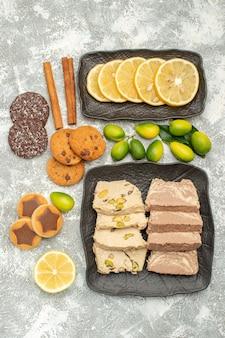 Bovenaanzicht van close-up snoepjes gesneden citroen zonnebloempitten halva kaneel koekjes