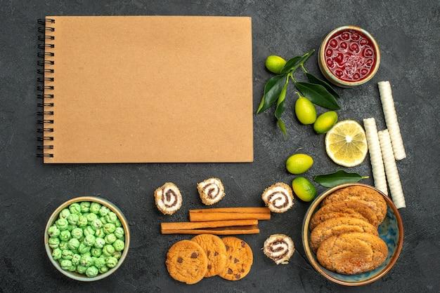 Bovenaanzicht van close-up snoepjes jam koekjes kleurrijke snoepjes kaneelstokjes crème notebook