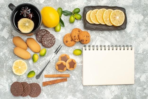 Bovenaanzicht van close-up snoepjes vork de smakelijke koekjes een kopje thee citrusvruchten notebook