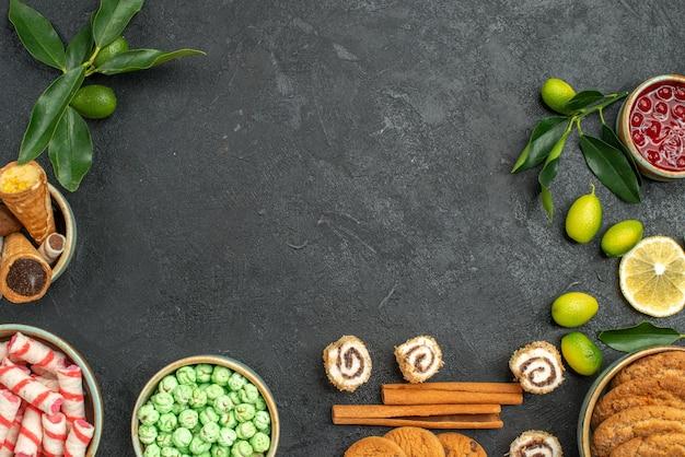Bovenaanzicht van close-up snoepjes wafels koekjes kleurrijke snoepjes jam kaneel citrusvruchten met bladeren