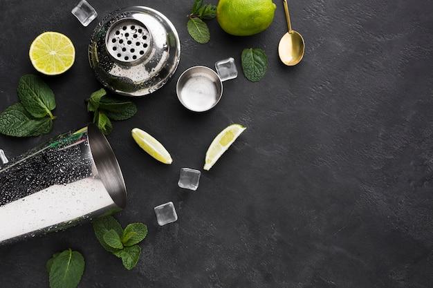 Bovenaanzicht van cocktail essentials met limoen en kopie ruimte