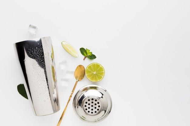 Bovenaanzicht van cocktail essentials met limoen en munt